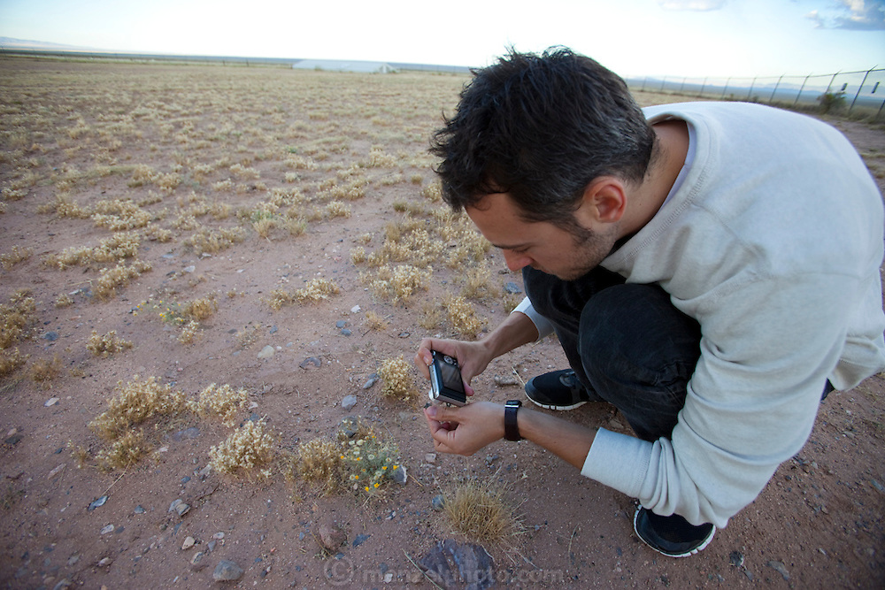 "Evan Menzel photographing trinitite at Site Trinity, ground zero, on the White Sands Missile Range in S. New Mexico. Site of the world's first atomic explosiion on August 6, 1945. The atomic bomb was developed by the Manhatten Project. The Manhattan Project refers to the effort during World War II by the United States, in collaboration with the United Kingdom, Canada, and other European physicists, to develop the first nuclear weapons. Formally designated as the Manhattan Engineering District (MED), it refers specifically to the period of the project from 1942-1946 under the control of the U.S. Army Corps of Engineers, under the administration of General Leslie R. Groves, with its scientific research directed by the American physicist J. Robert Oppenheimer. The project succeeded in developing and detonating three nuclear weapons in 1945: a test detonation on July 16 (the Trinity test) near Alamogordo, New Mexico; an enriched uranium bomb code-named ""Little Boy"" detonated on August 6 over Hiroshima, Japan; and a plutonium bomb code-named ""Fat Man"" on August 9 over Nagasaki, Japan. (http://en.wikipedia.org/wiki/Manhattan_Project) MODEL RELEASED."