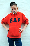 Girl wearing a gap jumper with a baby's dummy in her mouth