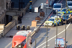 © Licensed to London News Pictures. 29/11/2019. London, UK.  Armed police officers point their weapons towards where the suspected attacker lies on the ground (bottom left) following a suspected terror attack on London Bridge. Several people were stabbed, at least two fatally, before armed police shot the attacker dead.  Photo credit: Cliff Hide/LNP