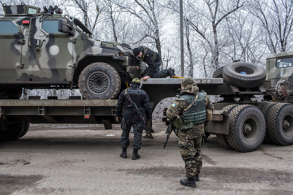 ARTEMIVSK, UKRAINE - FEBRUARY 14: Ukrainian soldiers secure a vehicle to a trailer at a checkpoint along the road toward the embattled town of Debaltseve on February 14, 2015 in Artemivsk, Ukraine. A ceasefire between Ukrainian forces and pro-Russian rebels is scheduled to go into effect at midnight. (Photo by Brendan Hoffman/Getty Images) *** Local Caption ***
