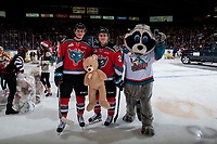 KELOWNA, CANADA - DECEMBER 2: Kaedan Korczak #6, and Kyle Topping #24 of the Kelowna Rockets stand with mascot Rocky Raccoon after the annual teddy bear toss against the Kootenay Ice on December 2, 2017 at Prospera Place in Kelowna, British Columbia, Canada.  (Photo by Marissa Baecker/Shoot the Breeze)  *** Local Caption ***