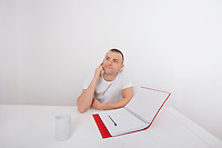 Thoughtful businessman answering smart phone at desk