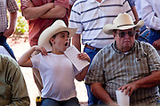 31 JULY 2009 --  BUCKEYE, AZ: Cutter Boyle (CQ) 6, yawns while he and his great uncle Bill Boyle (CQ) from Casa Grande, watch the bidding at the auction on the former Pylman Dairy Farm in Buckeye. The auction was handled by Overland Stockyards from Hanford, CA. The Arizona dairy industry is struggling to survive the worst milk economy some have ever seen. Due to the global recession, overseas demand for Arizona dairy products has plummeted, forcing prices down while production costs have stayed stable or gone up. For every $1 dairymen earn from milk sales, it cost them $1.50 to produce the milk. Photo by Jack Kurtz