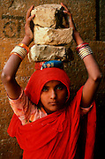 INDIA, PORTRAITS Portrait of a young Rajasthani girl carrying stones at construction in Jaisalmer