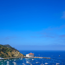 Catalina Island Avalon Harbor photo from above. Includes the Catalina Casino theater, Avalon Pier, and boats. Beautiful Santa Catalina Island is a popular travel destination off the Southern California coast. Photo is high resolution. Copyright ⓒ 2017 Paul Velgos with All Rights Reserved.