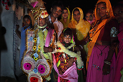 Kaushal and Rajni, 5, participate in a marriage ceremony, Rajasthan, India, April 28, 2009. Three young sisters Radha, 15, Gora, 13, and Rajni, 5, were married to their young grooms Aleen, Giniaj and Kaushal, who were also siblings, on the Hindu holy day of Akshaya Tritiya, called Akha Teej in north India. The auspicious day is said to bring good luck to couples married then and is widely known in Rajasthan as the day most child marriages occur. Despite legislation forbidding child marriage in India, such as the Child Marriage Restraint Act-1929 and the much more progressive Prohibition of Child Marriage Act of 2006, marrying children off at a very tender age continues to be accepted by large sections of society.