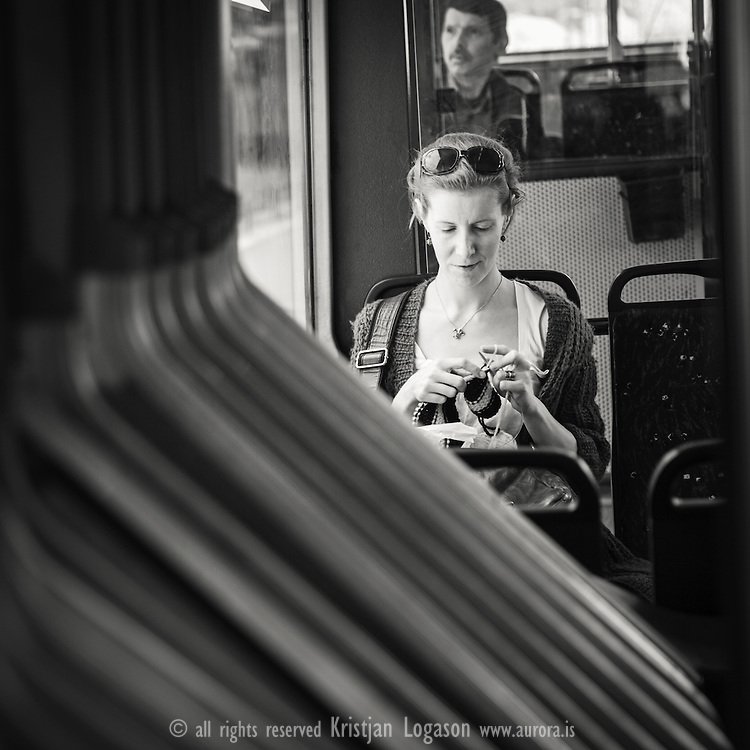 Smiling woman on a bus in Bergen using the travel time to knit