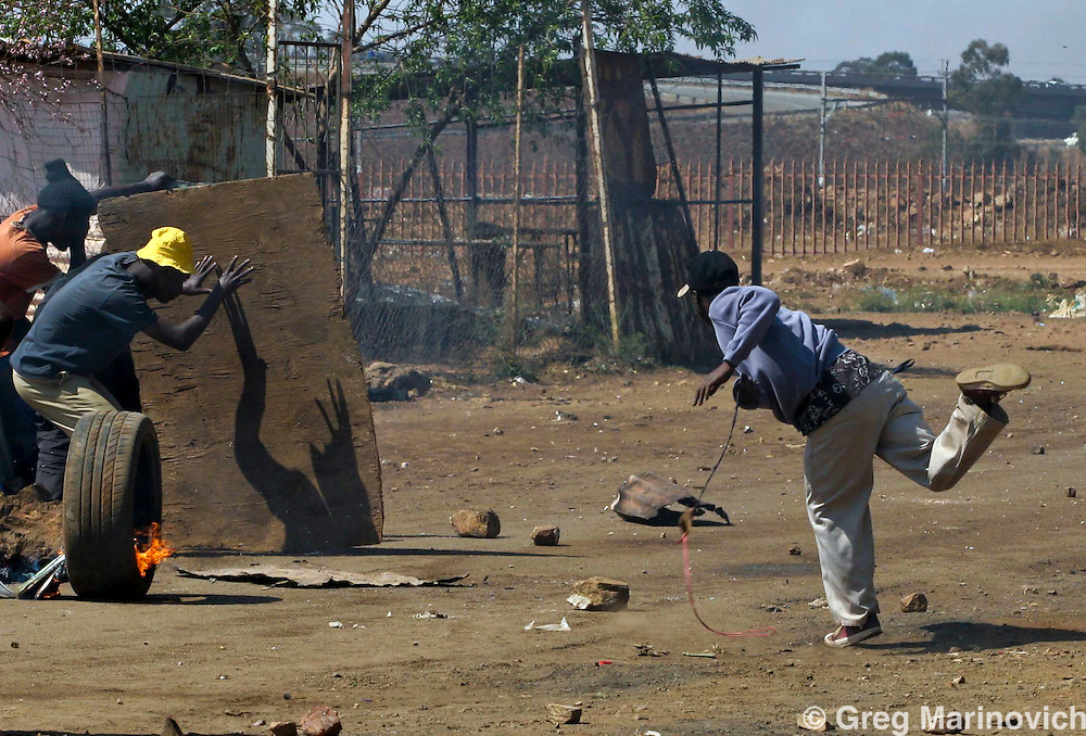 Residents of the informal settlement of Zone 1, Protea South use slingshots and duck rubber bullets as they battle with police in  aprotest against poor service delivery in the fields of water, electricity, housing,sanitation and health, Sept 1 2007.  Informal settlementsthat dot the Sebokeng/Evation area south of Johannesburg have been taking to the streets to protest lack of service delivery, or inadequate services that are not what they believe were promised them by the African National Congress before they came into power in 1994.  Photo Greg Marinovich
