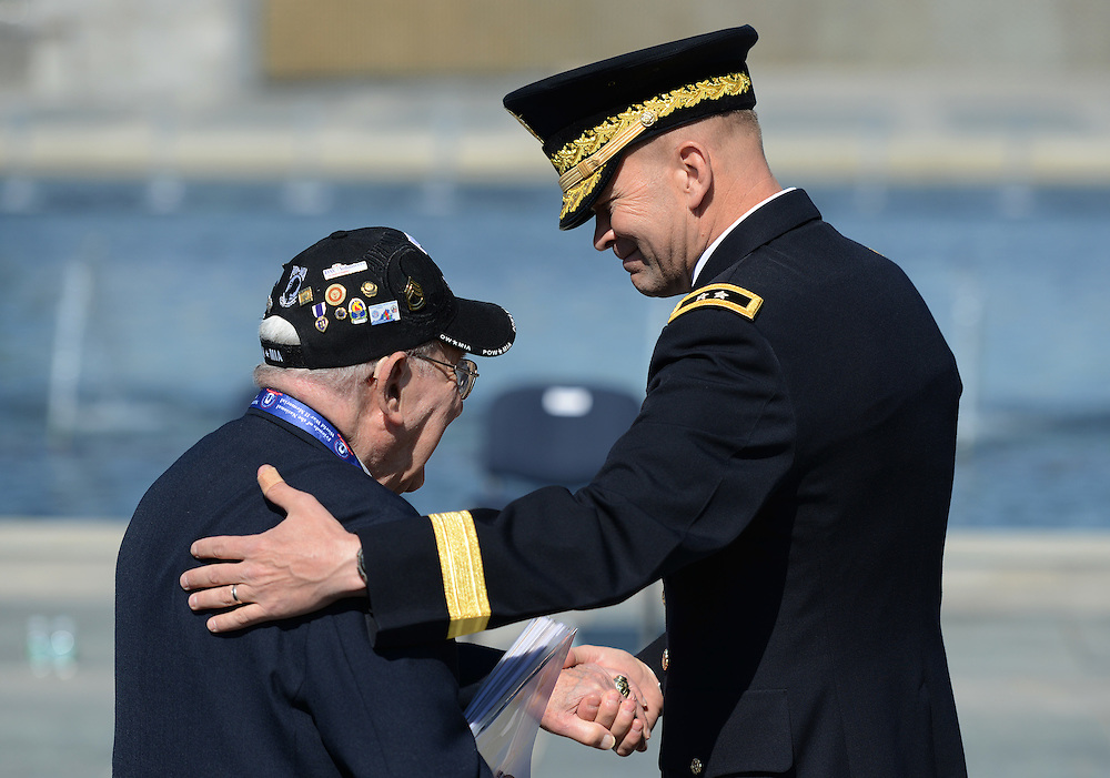 WWII veteran and FPOW Sgt. Jerry Wolf, of Springfield, Va., greets Major General Jeffrey Buchanan during a 10th anniversary ceremony for the WWII Memorial in Washington, Saturday, May 24, 2014.