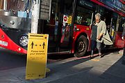 As the number of new Coronavirus cases in the UK climbs to 201,101, with UK deaths now standing at 30,076 - the highest recorded in Europe, passengers exits a bus towards to a Transport For London (TFL) sign asking the public to maintain safe social distances while travelling on the capital's public transport during the continuing Covid lockdown, on 6th May 2020, in south London, England. Front doors on London buses are now disabled to avoid exposure of drivers to the virus, plus no fares are being taken on journeys to further avoid card reader contact.