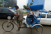 Young Indians go to work by rickshaw in New Delhi's new CBD is located in Gurgaon, an hour South of  the city