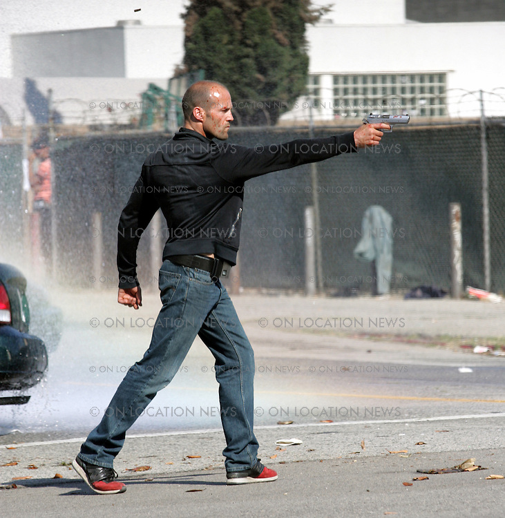 June 1st 2008  Los Angeles, CA.  EXCLUSIVE Photo..Jason Staham shoots a gun while filming a scene for Crank 2. During a filming break Statham checks his IPhone and visits with his girlfriend.  Photo by On Location News. Sales: Eric Ford 818-613-3955 info@onlocationnews.com..Photographer Code: ECF