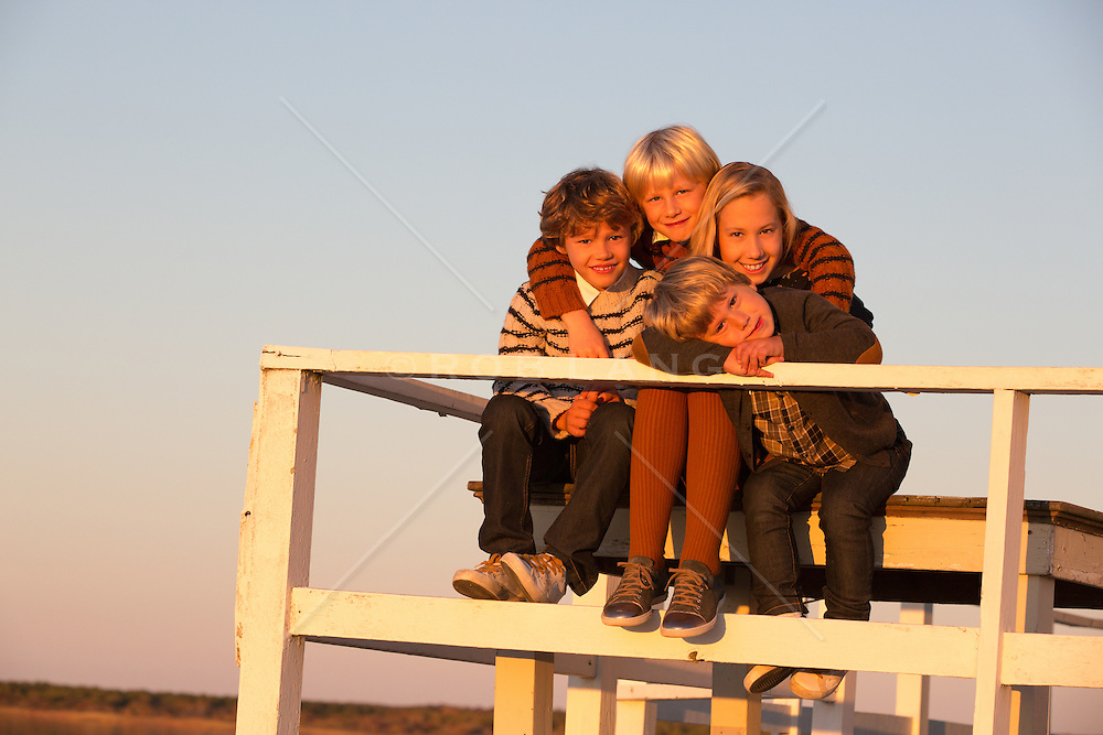 family of four children ages 4-9 years old, outdoors on a lake house deck at sunset