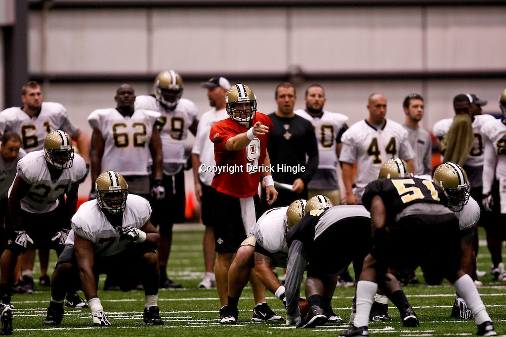 July 31, 2010; Metairie, LA, USA; New Orleans Saints quarterback Drew Brees (9) under center during a training camp practice at the New Orleans Saints indoor practice facility. Mandatory Credit: Derick E. Hingle