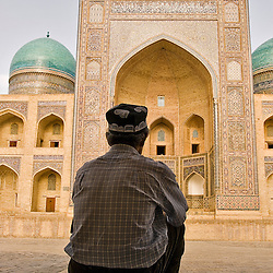 Man sitting down in front of the Mir-i-Arab madrassa, Bukhara, Uzbekistan, Asia