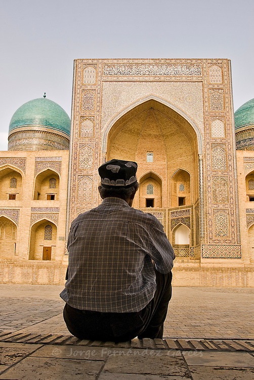 Man sitting down in front of the Mir-i-Arab madrassa, Bukhara, Uzbekistan, Asia