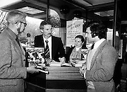 One of the most flamboyant and controversial heroes in the history of soccer, Derek Dougan signs copies of his autobiography, Doog, for customers at Hodges Figgis, Stephen&rsquo;s Court, Dublin. Photo shows one of the first customers, Peter Moynihan of Sandyford, County Dublin, as well as Robert Twigg, Manager, Hodges Figgis, and Norma Doyn, cashier.<br /> 16 April 1980