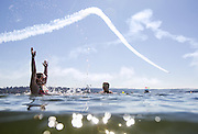 Swimmers in Lake Washington at Mount Baker Beach enjoy the Blue Angels practice, Thursday July 30, 2015.<br />