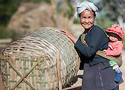 Country woman carrying son at her back while working on the fields (Myanmar)