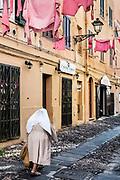Nun walks along a cobblestone street, Alghero,, Sardinia, Italy