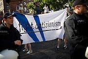 Mainz | 18 July 2014<br /> <br /> Am Samstag (18.07.2014) nahmen etwa 1000 M&auml;nner, Frauen und Kinder in der Innenstadt von Mainz anl&auml;sslich der milit&auml;rischen Auseinandersetzung zwischen Israel und der Hamas in Gaza an einer Solidarit&auml;tsdemonstration f&uuml;r Gaza, ein freies Pal&auml;stina und gegen Israel teil. Bei der Demo wurden Fahnen der Hamas und der Hisbollah mitgef&uuml;hrt, neben den &uuml;blichen Parolen gegen Israel wurde in Sprechch&ouml;hren auch vereinzelt zur Vernichtung von J&uuml;dinnen und Juden aufgerufen.<br /> Hier: Antifaschisten mit einem Transparent mit der Aufschrift &quot;Fight Antizionism&quot; am Rand der Demo.<br /> <br /> <br /> &copy;peter-juelich.com<br /> <br /> [No Model Release | No Property Release]