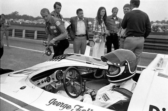 George Follmer in cockpit of Penske Porsche 917/10K at Mid-Ohio, 1972. In background from left are mechanic Woody Woodard, Porsche engineer Helmut Flegel, unknown gentleman, Mrs. Penske, unknown, Mark Donohue and (from rear) Roger Penske