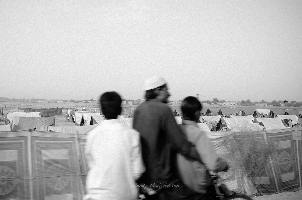 A father and two sons on a motorbike drive past one of the many camps for flood victims in Sukkur. Sukkur, Pakistan, 2010