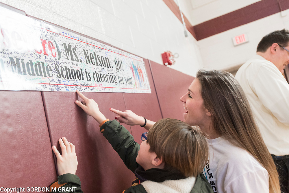 Cara Nelson, right, a 7th grade social studies teacher at the East Hampton Middle School, looks at a poster signed by students, during a sendoff in her honor, at the school in East Hampton, Jan. 18, 2018. Nelson will leave next week to participate in a trip where she will run seven marathons in seven days on seven continents.
