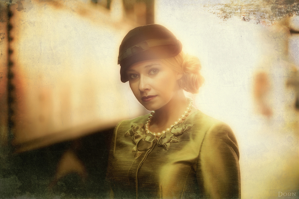 Vintage style photo in a train yard. Blonde Lady in 1950s fashion.