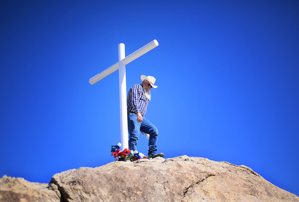 A military veteran stands next to the cross during an unveiling ceremony for the Mojave Cross on Veterans Day in Cima, California on Sunday, November 11, 2012.  A battle has been brewing for over Thirteen years over whether the cross can legally stay on Sunrise Rock because it violates Separation of Church and State and is in the Mojave National Perserve which is on Federal Lands.  The Veterans of Foreign Wars and American Legion Society raised money to purchase the plot of land and has kept the cross in place and today serves as war memorial.(Photo by Sandy Huffaker)