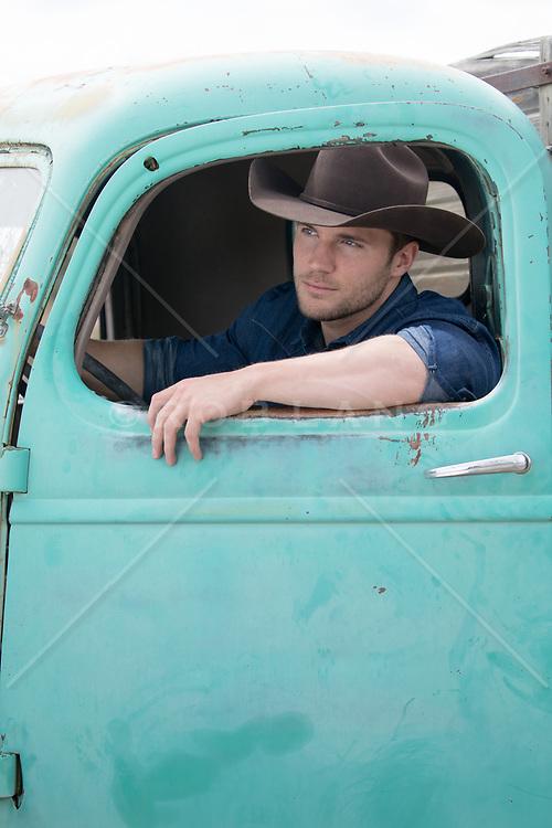 cowboy sitting in a rustic truck