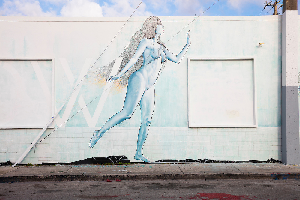 A softly-colored mural in Miami's Wynwood arts district depicting a nude woman, perhps the Eve to the Adam-like figure painted on an adjacent wall