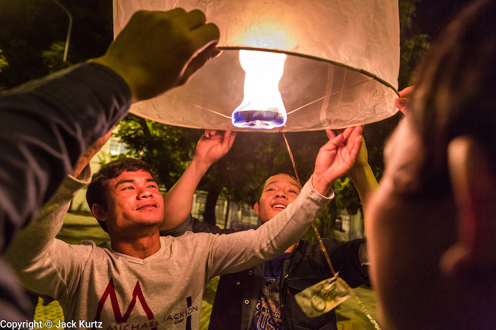 """17 NOVEMBER 2013 - BANGKOK, THAILAND: Thai laborers from northern Thailand luanch  a Yi Peng lantern on Loy Krathong near Wat Yannawa in Bangkok. The Yi Peng lanterns are Loy Krathong tradition in Chiang Mai but they are becoming more popular  in Bangkok and central Thailand. Loy Krathong (also written as Loi Krathong) is celebrated annually throughout Thailand and certain parts of Laos and Burma (in Shan State). The name could be translated """"Floating Crown"""" or """"Floating Decoration"""" and comes from the tradition of making buoyant decorations which are then floated on a river. Loi Krathong takes place on the evening of the full moon of the 12th month in the traditional and they do this all evening on the 12th month Thai lunar calendar. In the western calendar this usually falls in November. The candle venerates the Buddha with light, while the krathong's floating symbolizes letting go of all one's hatred, anger, and defilements       PHOTO BY JACK KURTZ"""