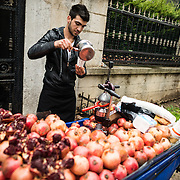 A main sells freshly squeeces pomegranate juice from his cart in Istanbul, Turkey.