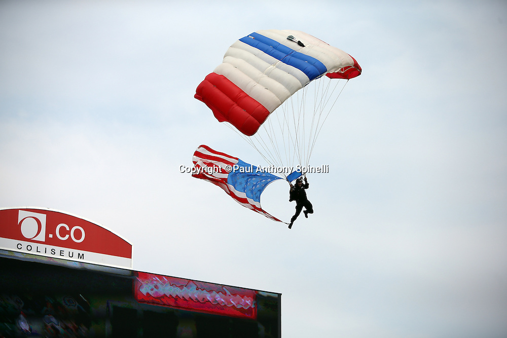 A member of the Frog-X parachute team parachutes into the stadium as part of pregame festivities before the Oakland Raiders 2015 NFL week 1 regular season football game against the Cincinnati Bengals on Sunday, Sept. 13, 2015 in Oakland, Calif. The Bengals won the game 33-13. (©Paul Anthony Spinelli)