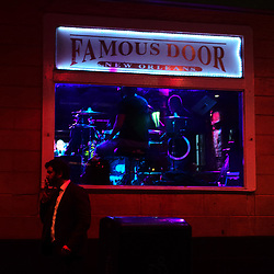 A man smoking walks past the Famous Door bar in the French Quarter, New Orleans, Louisiana, on Friday, Dec. 16, 2016.