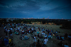 © Licensed to London News Pictures . 27/07/2018. London, UK. People gather on Primrose Hill hoping to catch sight of the blood red moon in total eclipse over London. Cloud cover meant that the moon wasn't seen. The rare phenomenon occurs when the Sun, the Earth and the Moon are in perfect alignment and the sun's light is refracted through the Earth's atmosphere whilst the Earth's shadow is cast over the moon . Photo credit: Peter Macdiarmid/LNP
