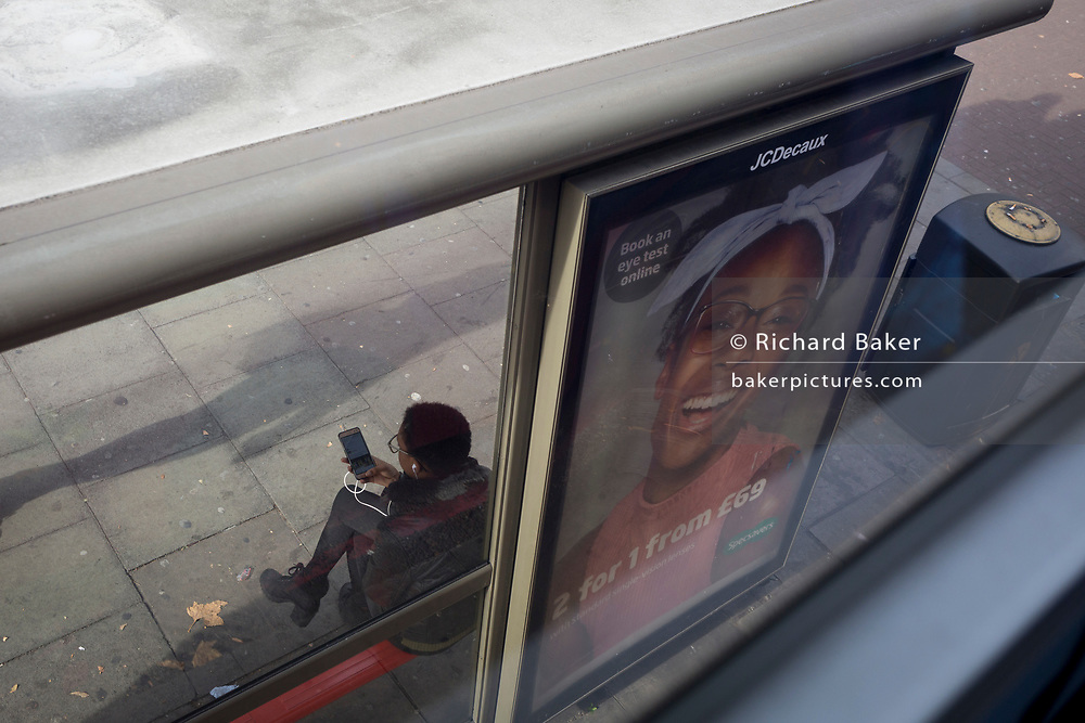 With her back to a bus shelter ad, a lady uses social media while waiting for a bus, on 30th October 2017, in the City of London, England.