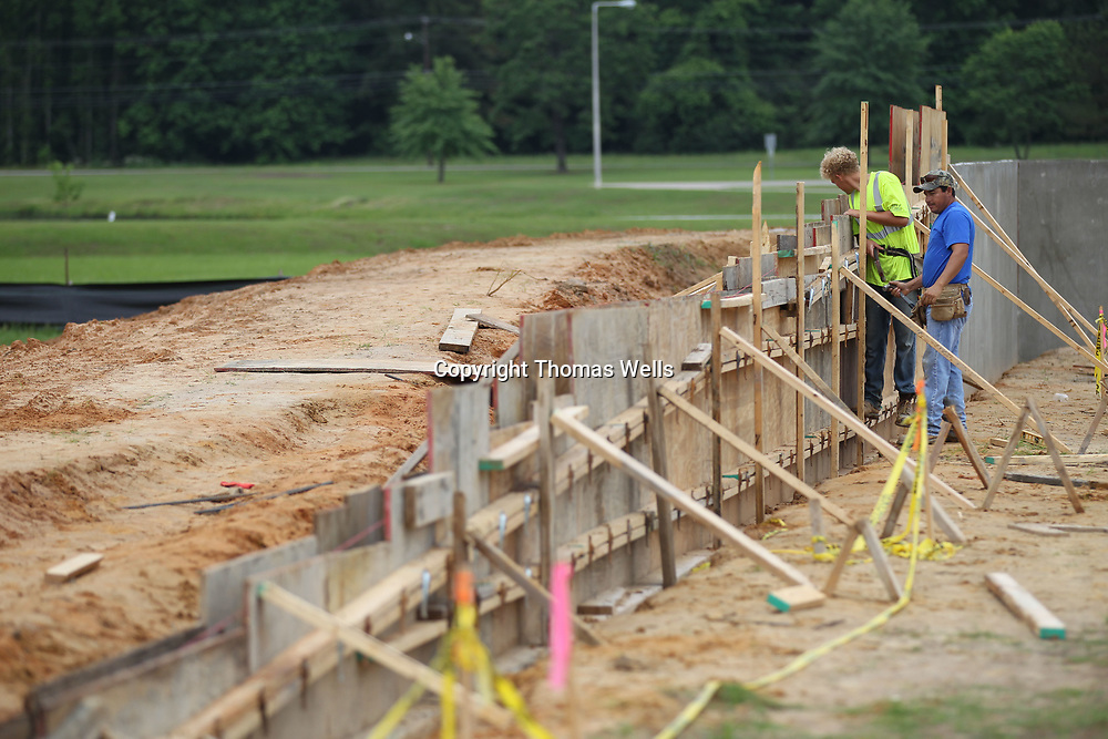 Michael Painter, left, and Orlando Casterlens continue building the wooden forms so they can pour the concrete to complete the new Vietnam Wall memorial under construction at Veterans Park on Tupelo.