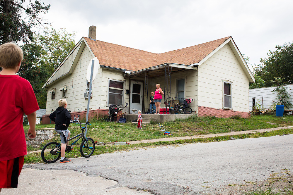 From her front porch, Delores Hilt watches her children and some of their neighborhood friends play after school.