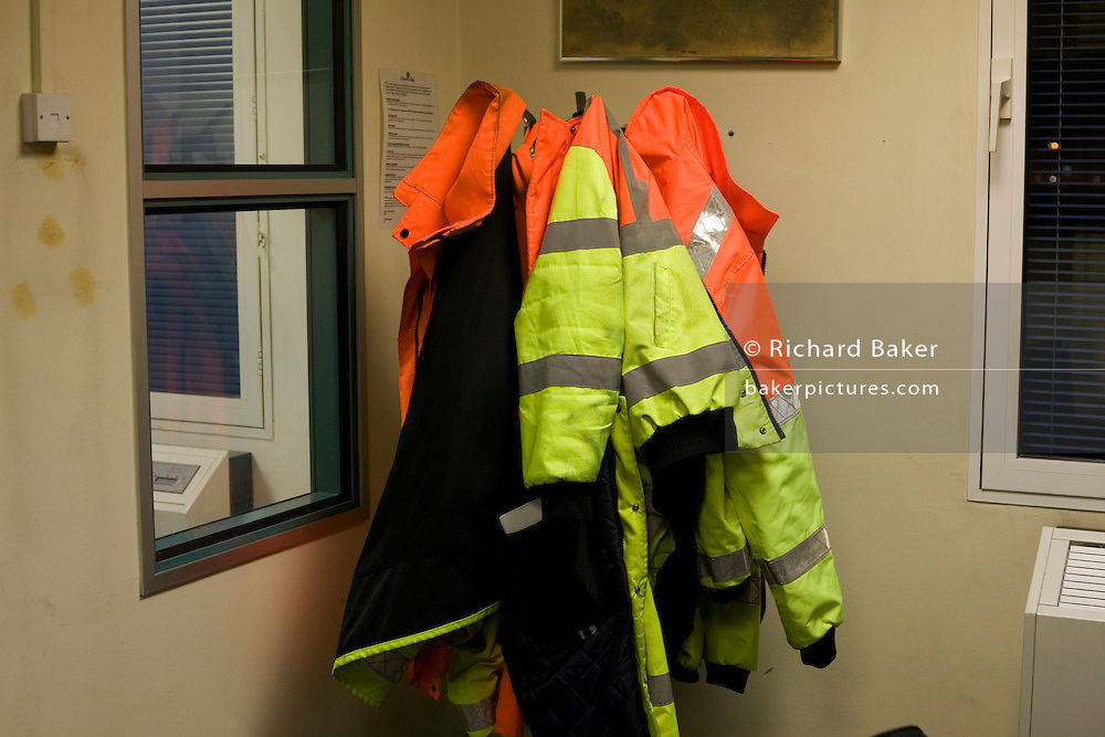 High-visibility jackets hang on a clothes stand belonging to Airside Operations Safety Unit (AOSU) staff at Heathrow airport.