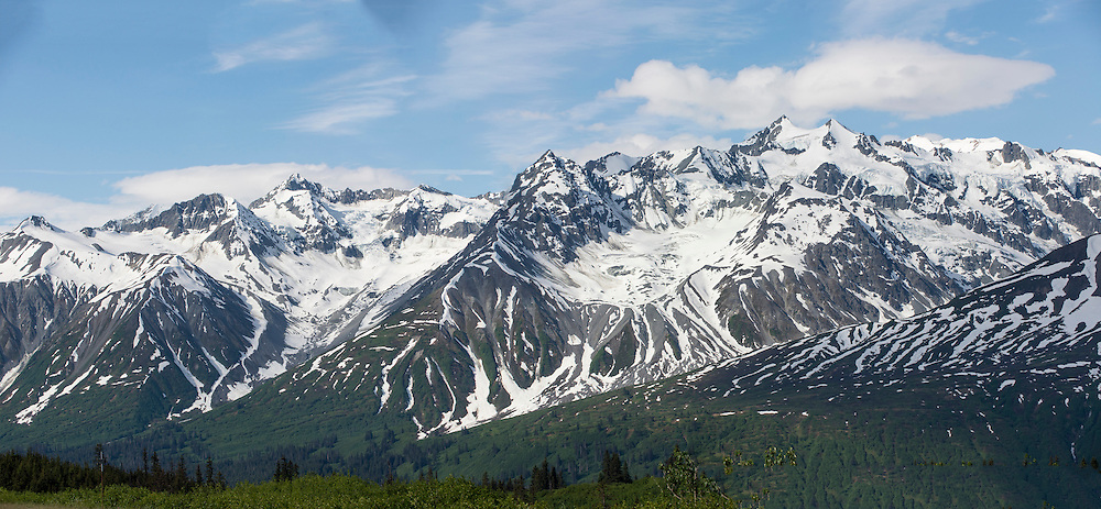 a panorama view of snow capped and glaciated mountains on a birght sunny day along the Haines Highway near the Alaska - British Columbia border