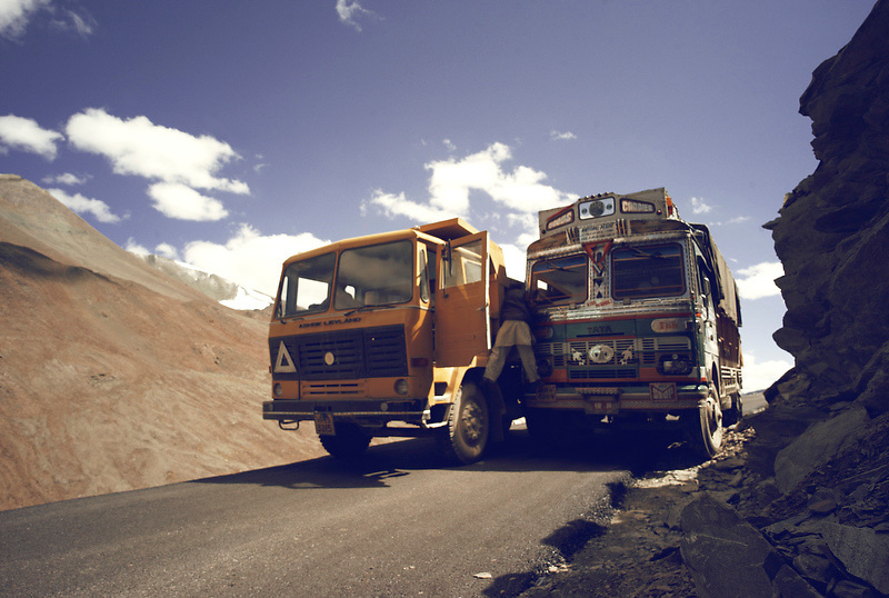 A truck attempts to pass another at a narrow pass with one driver hanging between the trucks giving guidance above the town of Keylong, capital of the Lawaul Bhage region, India on Sep 9, 2007. Off the side of the ride is  600m sheer drop to the valley below.