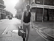 Young woman walking in empty street carrying her guitar case.