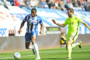 Wigan Defender Donervon Daniels takes on Southend United defender, Sam McQueen (20) during the Sky Bet League 1 match between Wigan Athletic and Southend United at the DW Stadium, Wigan, England on 23 April 2016. Photo by John Marfleet.