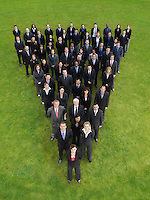 Large group of business people standing in triangle formation elevated view