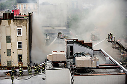 ".-A three-alarm fire ripped through a row of stores this morning near the corner of East 14th Street and Avenue A, authorities said..The fire began at 10:15 a.m.at 509 East 14th St., although the cause was not immediately known, fire officials said..Essa Assabahi, 29, who works at Stuyvesant Convenience, watched from across the street as the shop burned..""That's my job right there,"" he said. ""Now I'm unemployed."".The flames shot up from the roof and sent thick black clouds of smoke across a part of the East Village, tying up traffic and forcing people to cover their mouths as they tried to cross nearby streets...FDNY members fight the blaze on 14th Street...Assabahi said he saw smoke seeping out of the ceiling at 10:20 a.m..""I knew not to mess around with it,"" he said.After a futile attempt with a fire extinguisher to try and put out the fire, he and three of his co-workers ran outside..Adal Murshed, 35, who was also in the store at the time, said, ""A customer ran in and said, 'Get the heck out.' Then we started to see smoke and we just ran out."".Assabahi and the others called 911. Moments later, the entire store was ablaze..The fire reached three alarms about 45 minutes later and it took nearly 140 firefighters to douse the flames, fire officials said..Two firefighters was treated for smoke inhalation, officials said..Numan Hauter, 50, whose father owned the convenience store for 20 years, called the blaze ""a nightmare."".""What can you do?"" he said.."