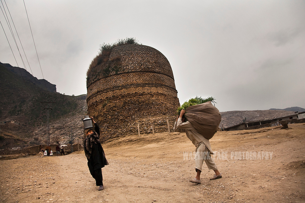 Local villagers carry their produce past the Shingardar Stupa in the Swat Valley, on February 11, 2011, in Gumbatuna, Pakistan. The Kingdom of Gandhara lasted from early 1st millennium BC to the 11th century AD, and was located in northern Pakistan and eastern Afghanistan. (Photo by Warrick Page)