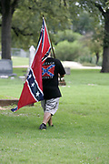 A lone protester who sympathizes with keeping Confederate statues at the Confederate Cemetery in Dallas walks between  graves on Saturday August 19, 2017. Hundreds of anti supremacist protesters gathered to denounce white supremacists and Donald Trump vastly outnumbering a handful of Confederate supporters.