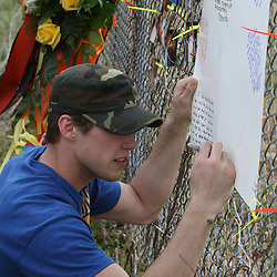 (Shot on March 6, 2009) Chris Hill writes on a memory wall put up on a fence along side the scene of a fatal hit and run accident that involved Hill's roommate Thurman Lowe who was one of three students killed while walking home shortly after 2:00am on the morning of March 6, 2008 on Nashville Street in Hammond, Louisiana after a drunk driver hit five students killing three and critically injuring one and leaving one student with minor injuries, the driver identified as 21-year-old Derek Quebedeaux also a Southeastern student was arrested by Hammond Police. Quebedeaux was also a roommate of Lowe and Hill.. (Photo by: Derick Hingle)